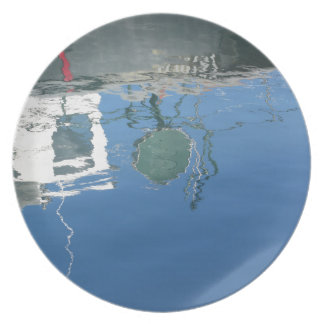Fishing boat reflects in the water plate