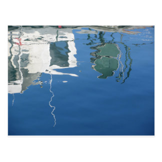 Fishing boat reflects in the water postcard