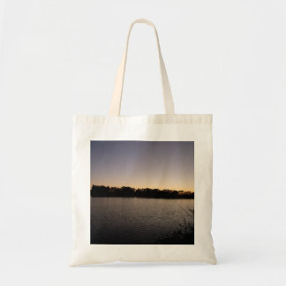 Fishing poles silhouette against the sun set budget tote bag
