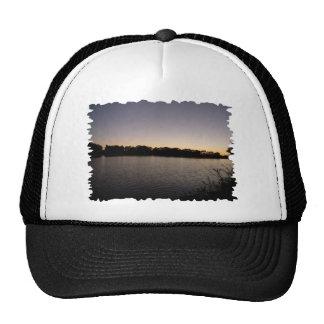 Fishing poles silhouette against the sun set cap