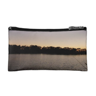Fishing poles silhouette against the sun set makeup bag