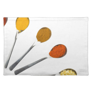 Five seasoning spices on metal spoons placemat