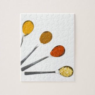 Five seasoning spices on metal spoons puzzle