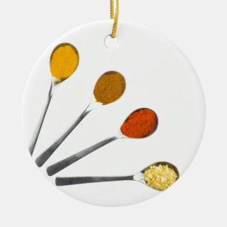 Five seasoning spices on metal spoons round ceramic decoration