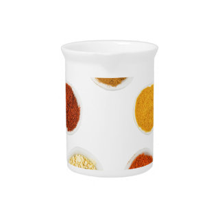 Five seasoning spices on porcelain spoons pitcher