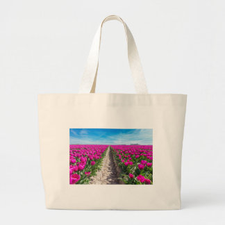 Flowers field with purple tulips and path large tote bag