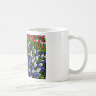 Flowers field with red blue tulips and hyacinths coffee mug