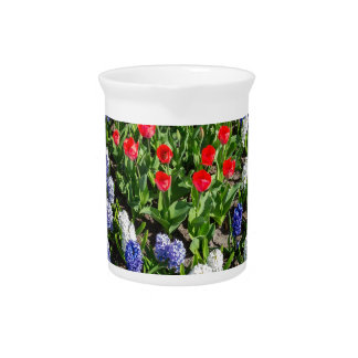 Flowers field with red blue tulips and hyacinths pitcher