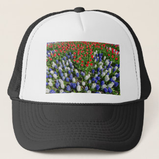 Flowers field with red blue tulips and hyacinths trucker hat