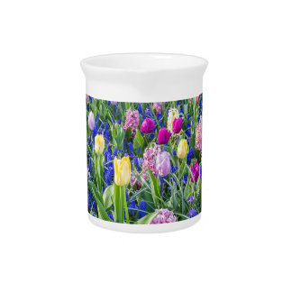 Flowers field with tulips hyacinths and bridge pitcher