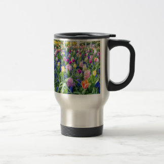 Flowers field with tulips hyacinths and bridge travel mug