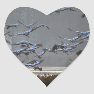 Flying cranes on a lake heart sticker