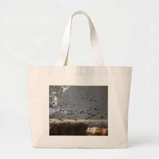 Flying cranes on a lake large tote bag