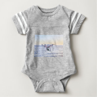 Flying drone at coast above sea baby bodysuit