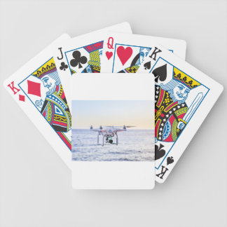 Flying drone at coast above sea bicycle playing cards