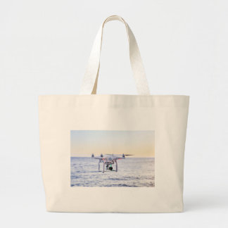 Flying drone at coast above sea large tote bag