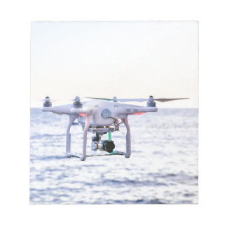 Flying drone at coast above sea notepad