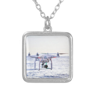 Flying drone at coast above sea silver plated necklace