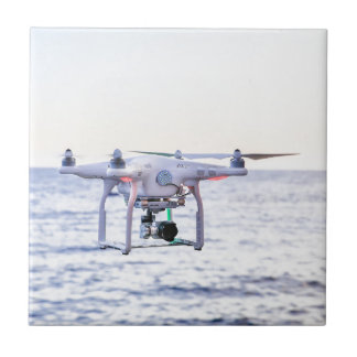 Flying drone at coast above sea tile