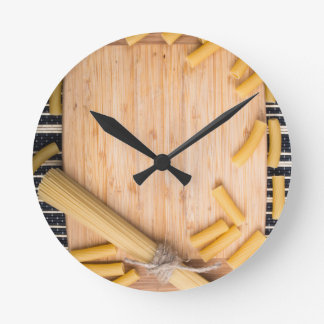 Food background with thin spaghetti and pasta round clock