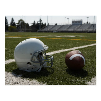 Football and football helmet on football field postcard