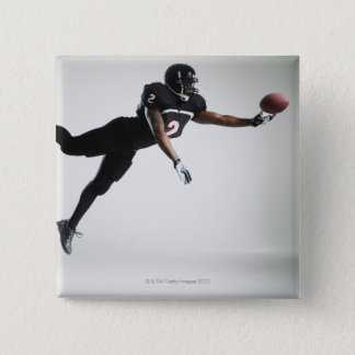 Football player leaping in mid air to catch ball 15 cm square badge