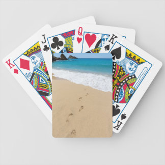 Footsteps in sandy beach leading to blue sea bicycle playing cards