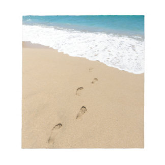 Footsteps in sandy beach leading to blue sea notepad