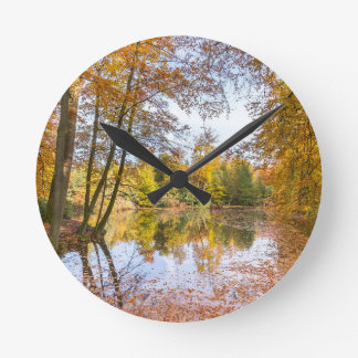 Forest pond covered with leaves in winter season wall clock