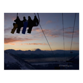 Four snowboarders are silhouetted on a ski lift postcard