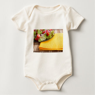 Fragment of a transparent plate closeup with salad baby bodysuit