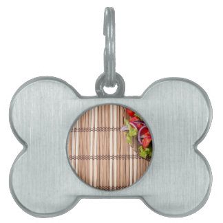 Fragment of a transparent plate of fresh salad pet name tag