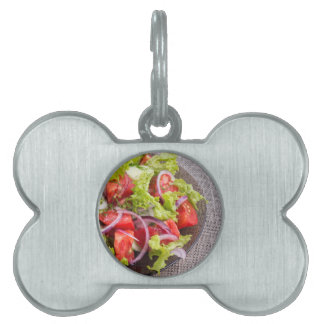 Fragment of a transparent plate with a fresh salad pet tag