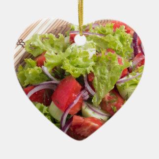 Fragment of vegetarian salad from fresh vegetables ceramic heart decoration