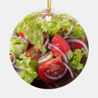 Fragment of vegetarian salad from fresh vegetables round ceramic decoration