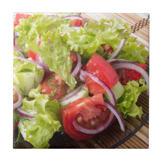 Fragment of vegetarian salad from fresh vegetables small square tile