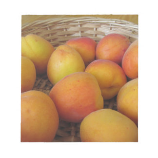 Fresh apricots in a wicker basket notepad