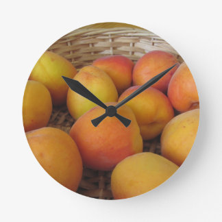 Fresh apricots in a wicker basket round clock