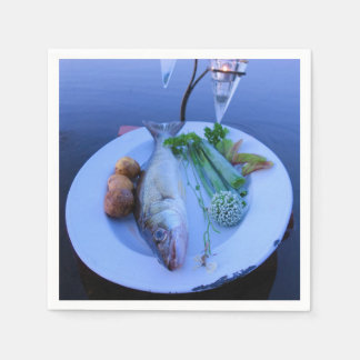 Fresh fish catch on a plate with vegetables paper napkins