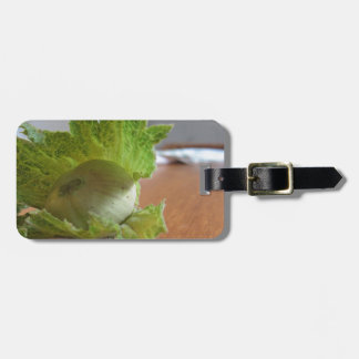 Fresh green hazelnuts on a wooden table luggage tag