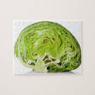 Fresh iceberg lettuce cut in half, on white puzzles