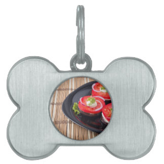 Fresh sliced tomatoes on a black plate close-up pet ID tag