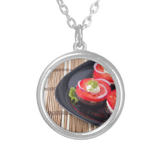 Fresh sliced tomatoes on a black plate close-up silver plated necklace