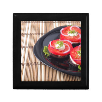 Fresh sliced tomatoes on a black plate close-up small square gift box