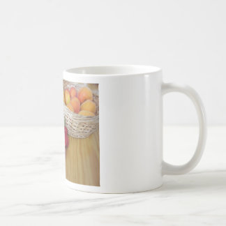 Fresh summer fruits on light wooden table coffee mug