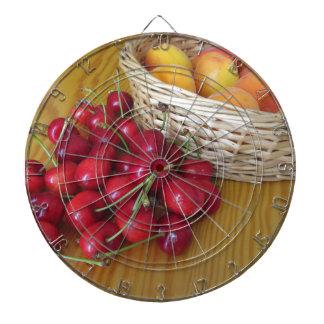 Fresh summer fruits on light wooden table dartboard