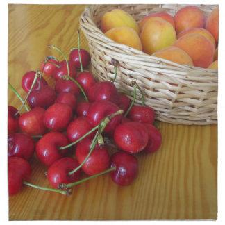 Fresh summer fruits on light wooden table napkin