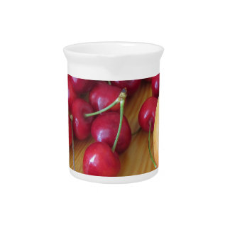 Fresh summer fruits on light wooden table pitcher