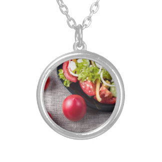 Fresh tomatoes and a part of a plate silver plated necklace