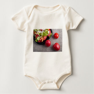 Fresh tomatoes and a part of a plate with salad baby bodysuit